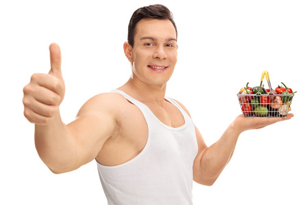 hand basket: Guy holding a small shopping basket full of fruits and vegetables and giving a thumb up isolated on white background Stock Photo