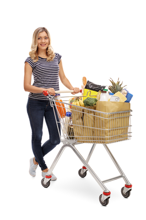 cart: Full length portrait of a woman posing with a shopping cart full of groceries isolated on white background Stock Photo