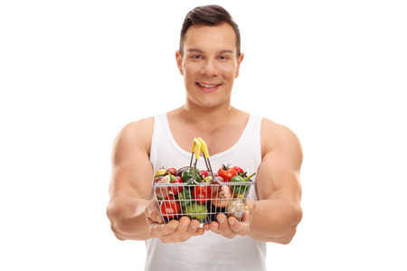 fruit basket: Smiling man offering a small shopping basket full of fruits and vegetables isolated on white background