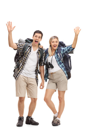 Full length portrait of two happy hikers waving at the camera isolated on white background Stock Photo