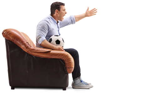 Annoyed man seated on an armchair watching football and yelling isolated on white background