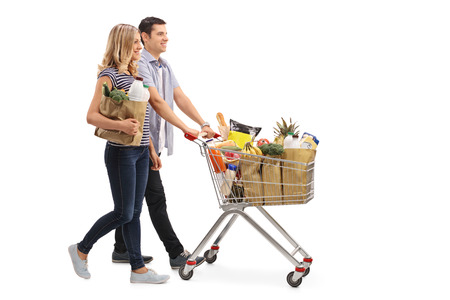 filled: Full length profile shot of a young couple pushing a shopping cart full of groceries isolated on white background