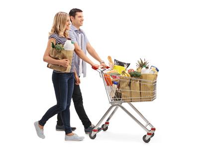 empujando: Tiro lleno perfil longitud de una pareja de jóvenes empujando un carrito de la compra lleno de comestibles aisladas sobre fondo blanco