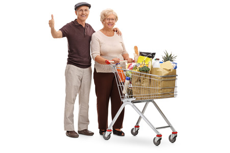shopping cart: Full length portrait of an elderly couple posing with a shopping cart and giving a thumb up isolated on white background