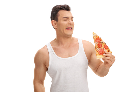 nauseous: Disgusted young guy looking at a slice of pizza isolated on white background