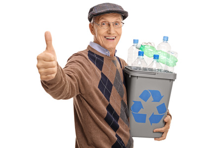 Cheerful mature man holding a recycling bin full of plastic bottles and giving a thumb up isolated on white background Stock Photo