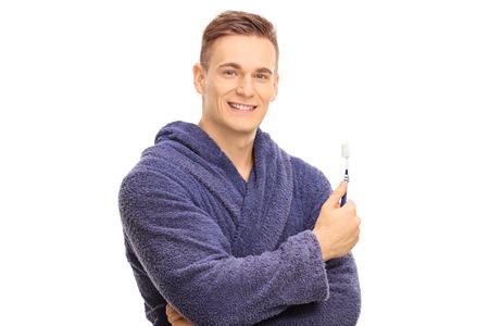 limpieza: Individuo hermoso en una albornoz que sostiene un cepillo de dientes aislados sobre fondo blanco