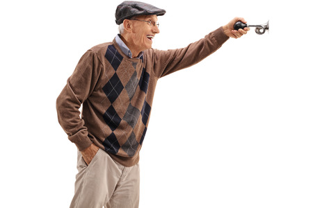 honking: Excited elderly man honking a horn isolated on white background Stock Photo