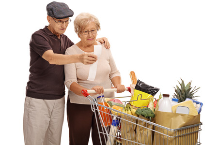 pricey: Shocked elderly couple looking at a store receipt isolated on white background Stock Photo