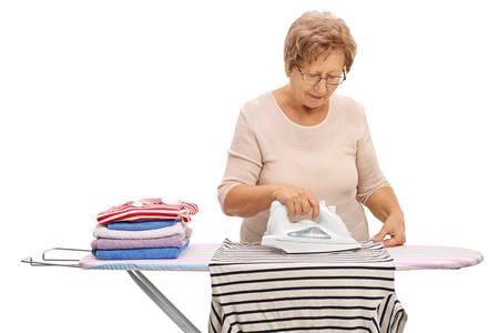 Donna matura stirare i vestiti su un asse da stiro isolato su sfondo bianco