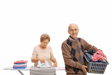 man laundry: Cheerful elderly man holding a laundry basket and a mature woman ironing isolated on white background Stock Photo