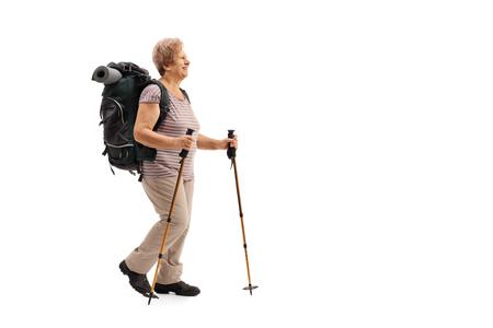 De volledige lengte profiel shot van een vrouwelijke volwassen wandelaar die op een witte achtergrond