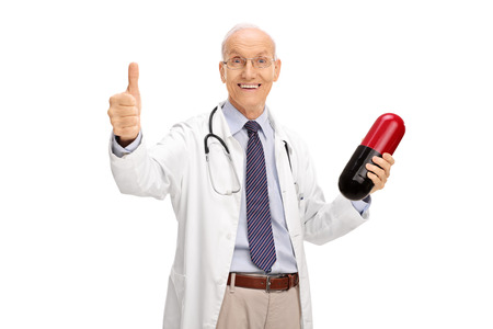 doctor giving glass: Joyful elderly doctor holding a big pill and giving a thumb up isolated on white background Stock Photo
