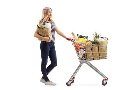 Perfil de cuerpo entero disparó a una mujer joven esperando en la cola con un carrito de compras y una bolsa de papel aislado en el fondo blanco
