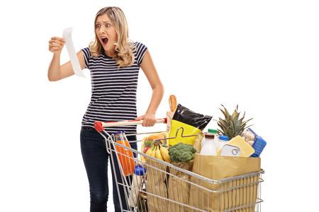 sorprendido: mujer joven sorprendido mirando a un recibo de la tienda aislado en el fondo blanco
