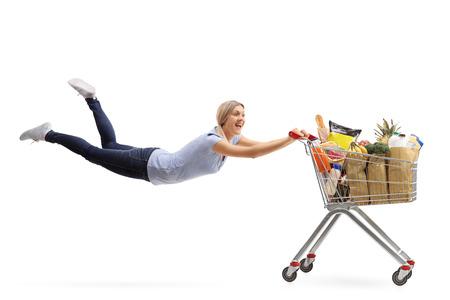 Happy vrouw wordt getrokken door een winkelwagentje vol met boodschappen op een witte achtergrond