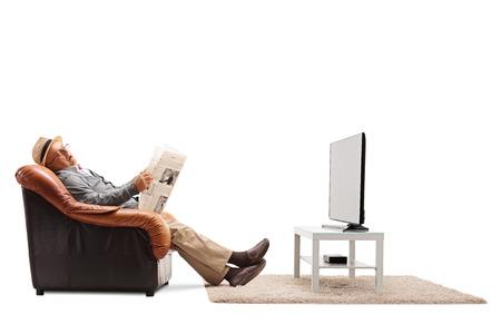 Bejaarde man zittend op een stoel met een krant en slapen in de voorkant van de tv op een witte achtergrond
