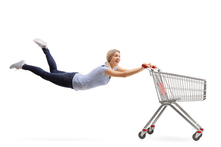 cart: Excited woman being pulled by an empty shopping cart isolated on white background