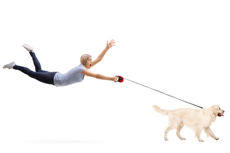 Young woman being pulled by her dog isolated on white background