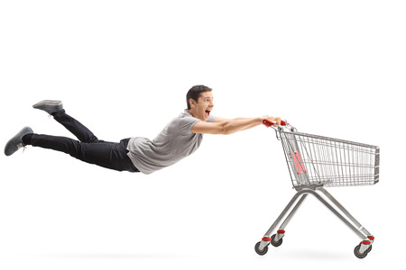 Young guy being pulled by an empty shopping cart isolated on white background