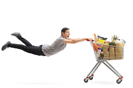 shopping cart: Young man being pulled by a shopping cart full of groceries isolated on white background