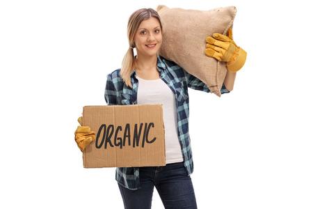 袋を運ぶと有機の孤立した白い背景を言う段ボール看板を持っている女性の農業労働者