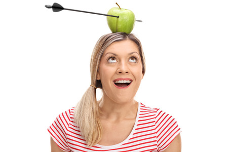 Overjoyed woman looking at an apple pierced by an arrow on her head isolated on white background