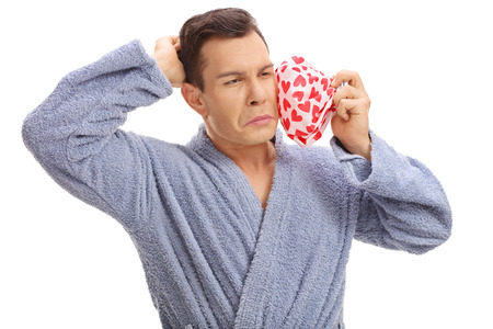 experiencing: Young man experiencing a toothache and holding an icepack isolated on white background