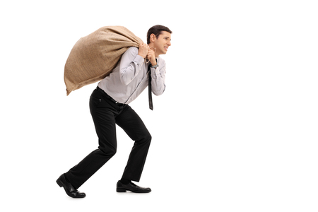 Full length profile shot of a businessman carrying a sack isolated on white background