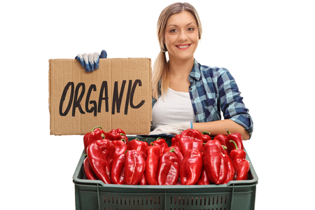 farmer sign: Happy female farmer posing with a crate full of peppers and a cardboard sign that says organic isolated on white background