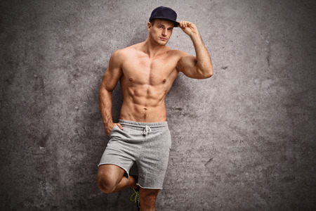 Handsome shirtless man leaning against a rusty gray wall and looking at the camera photo