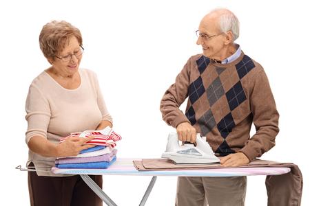 elderly woman: Senior couple ironing together isolated on white background Stock Photo