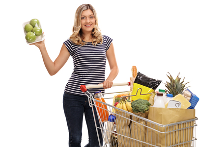 Young woman posing with a pack of apples and a shopping cart full of groceries isolated on white background Stock Photo