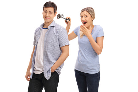 honking: Woman pranking her boyfriend by honking a horn next to his ear isolated on white background
