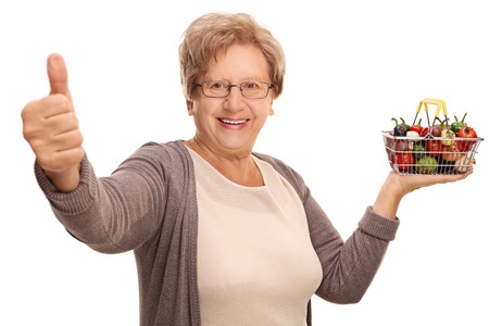 Happy mature woman holding a small shopping basket full of fruits and vegetables and giving a thumb up isolated on white background