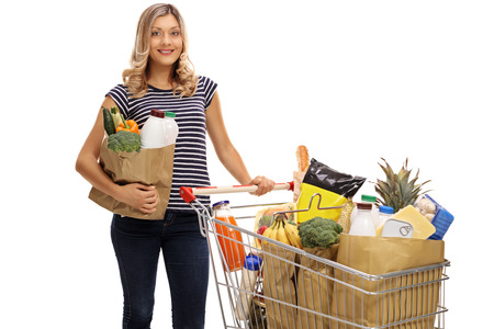 cart: Young woman posing with a shopping bag and a shopping cart full of groceries isolated on white background Stock Photo