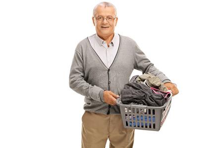 man laundry: Elderly man holding a laundry basket full of clothes isolated on white background Stock Photo