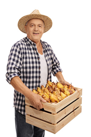 Elderly farmer holding a crate filled with pears isolated on white background