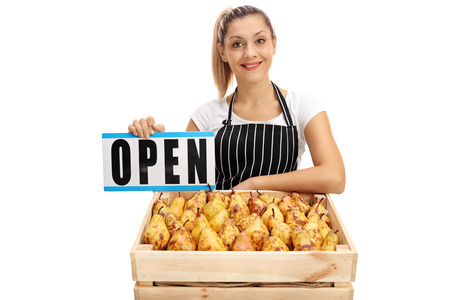isolated sign: Joyful female vendor posing with a crate full of pears and an open sign isolated on white background Stock Photo