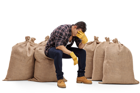 sackful: Depressed farmer sitting on a burlap sack and holding his head in disbelief isolated on white background Stock Photo
