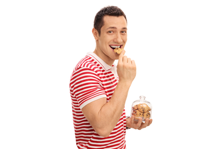 Young guy eating a cookie and holding a cookie jar isolated on white background Archivio Fotografico