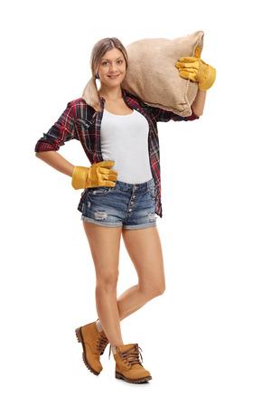 Portrait en pied d'un fermier femme posant avec un sac de jute isolé sur fond blanc
