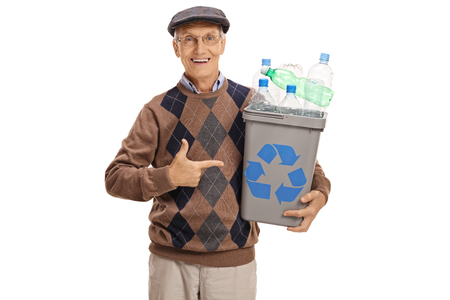 Cheerful elderly man holding a recycling bin full of plastic bottles and pointing isolated on white background