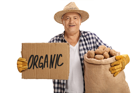 Elderly farmer holding a burlap sack full of potatoes and a cardboard sign that says organic isolated on white background Stock Photo