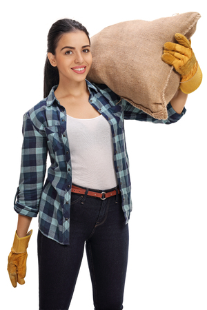 sackful: Happy female agricultural worker holding a burlap sack on her shoulder isolated on white background Stock Photo