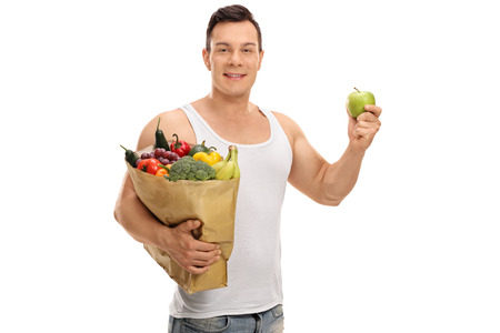 Young man holding a shopping bag full of fruits and vegetables and an apple isolated on white background