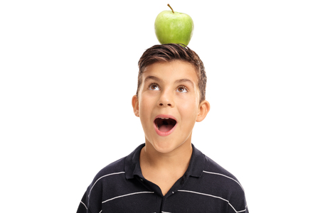 overjoyed: Overjoyed little boy looking at an apple on his head isolated on white background