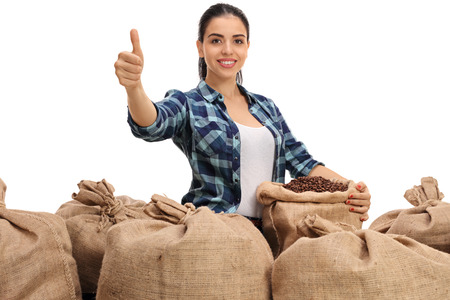 sackful: Cheerful female farmer posing with burlap sacks filled with coffee beans and giving a thumb up isolated on white background Stock Photo