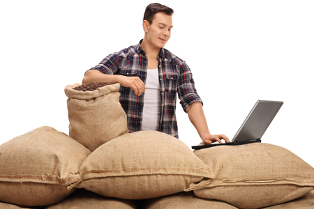 sackful: Agricultural worker posing with burlap sacks filled with coffee beans and working on a laptop isolated on white background Stock Photo