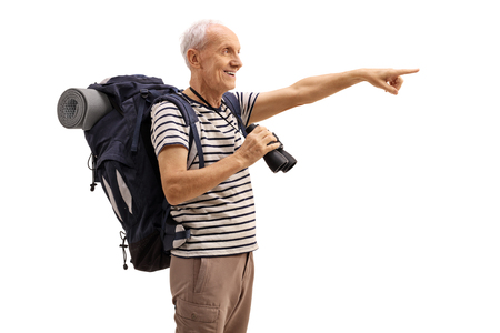distance: Mature hiker holding a binoculars and pointing in the distance isolated on white background